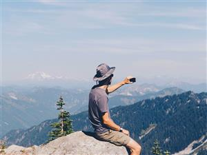 Man taking picture on the top of a mountain
